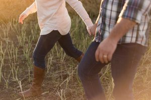 two person wearing denim pants on grass field