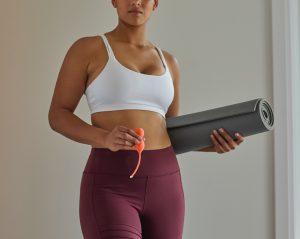 woman in white sports bra and purple leggings holding black speaker