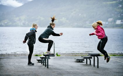 woman in pink jacket and black pants jumping on black bench near body of water during